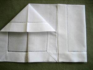Take hold of the inner left edge of the napkin and pull it out to form a tent like shape & Folding a Napkin Into a Cap